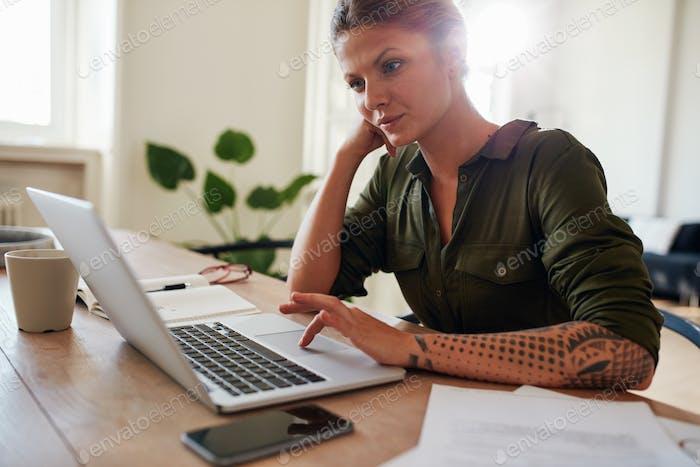 Женщина, работающая из дома, используя ноутбук