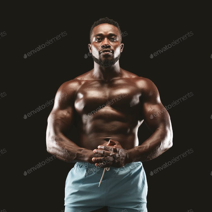 Portrait of muscular sportsman demonstrating his body over black background