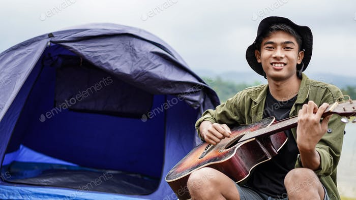 Reisender spielt Gitarre im Camp
