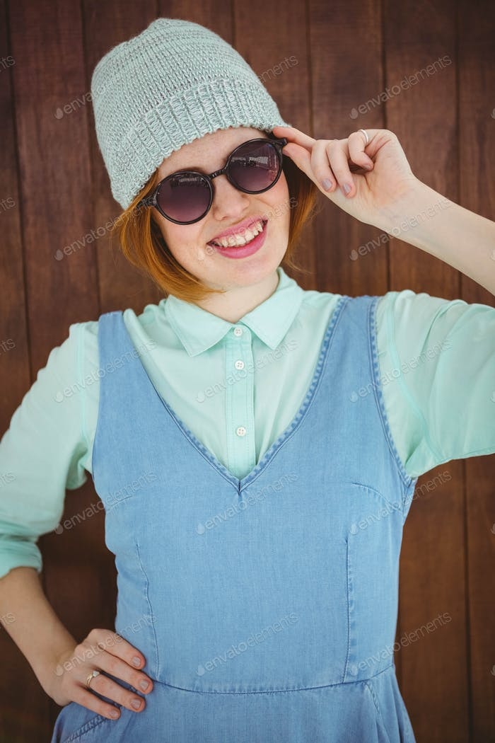 Red haired hipster posing on wooden background
