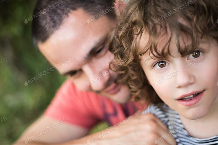 Young father with his son. Sunny summer nature.