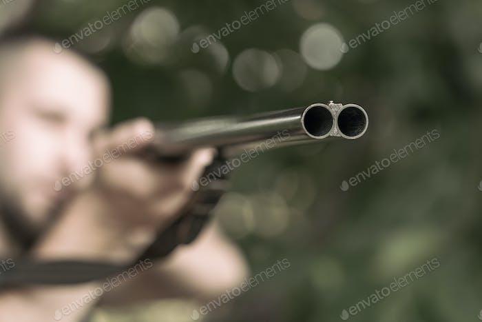 Mann, der ein Gewehr zielt
