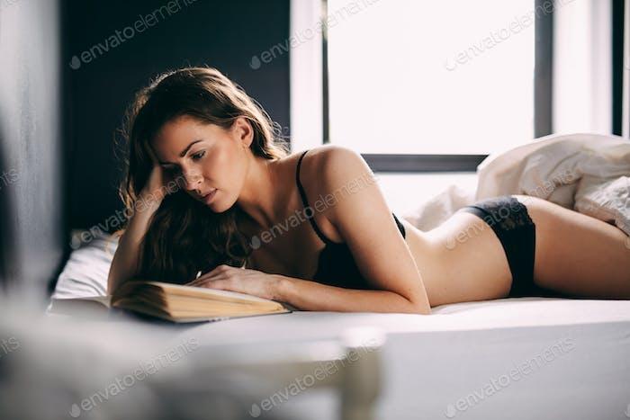 Young brunette in lingerie reading novel in bedroom