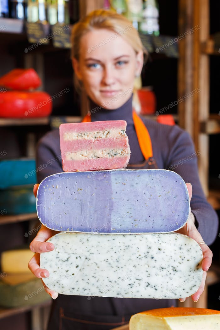 Large pieces of cheese in shop assistant hands