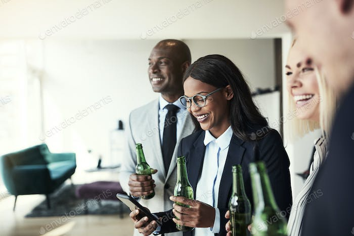 Smiling businesswoman checking her cellphone during after work drinks