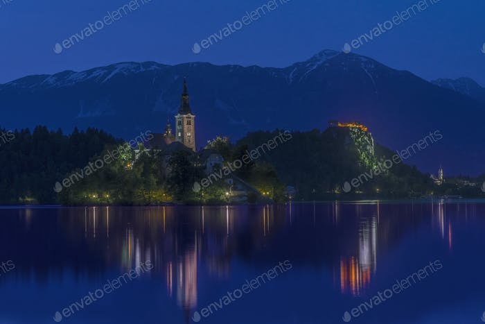 Village church and buildings reflected in still lake at night, Bled, Upper Carniola, Slovenia