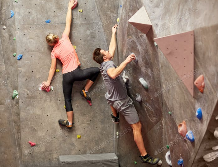 man and woman training at indoor climbing gym wall