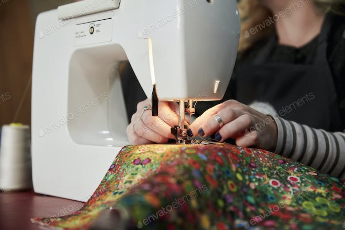 A woman threading a needle on a sewing machine, sewing upholstery fabric.