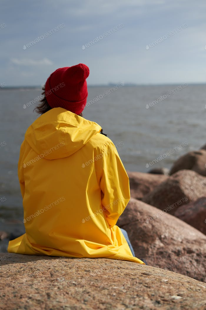 Back view of woman sitting in bright yellow cloak and red hat on stone near shore of North sea