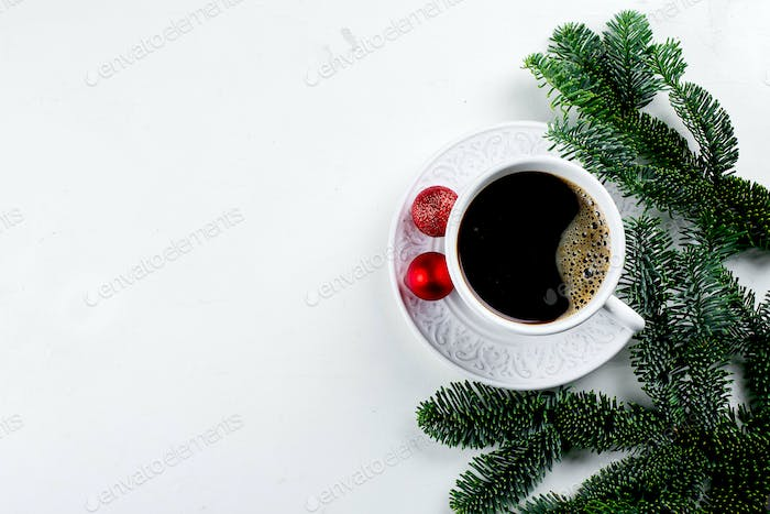 Cup of black coffee and spruce branch on white background. Top view, copy space