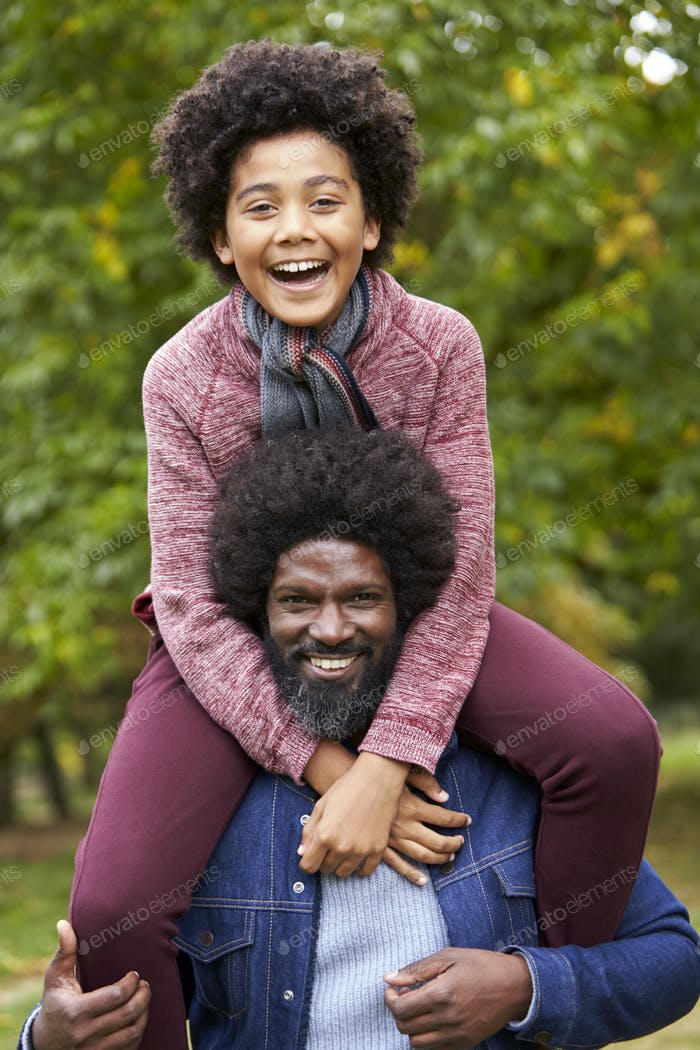 Black middle aged man carrying his son on his shoulders in the park, smiling to camera