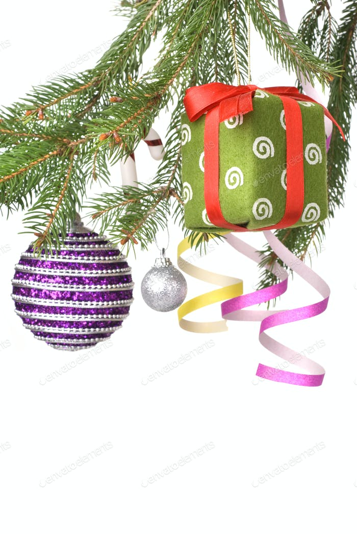Christmas balls, gift and decoration on fir tree branch isolated