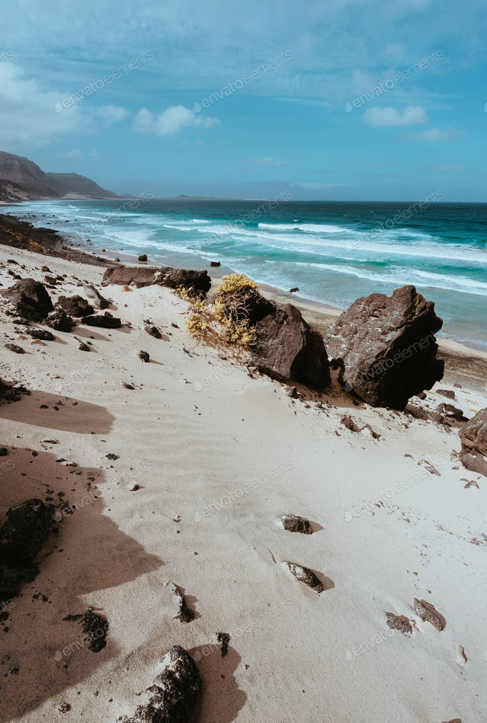 Huge volcanic stone boulder on spectacular white sand dunes of remote deserted beach Praia Grande