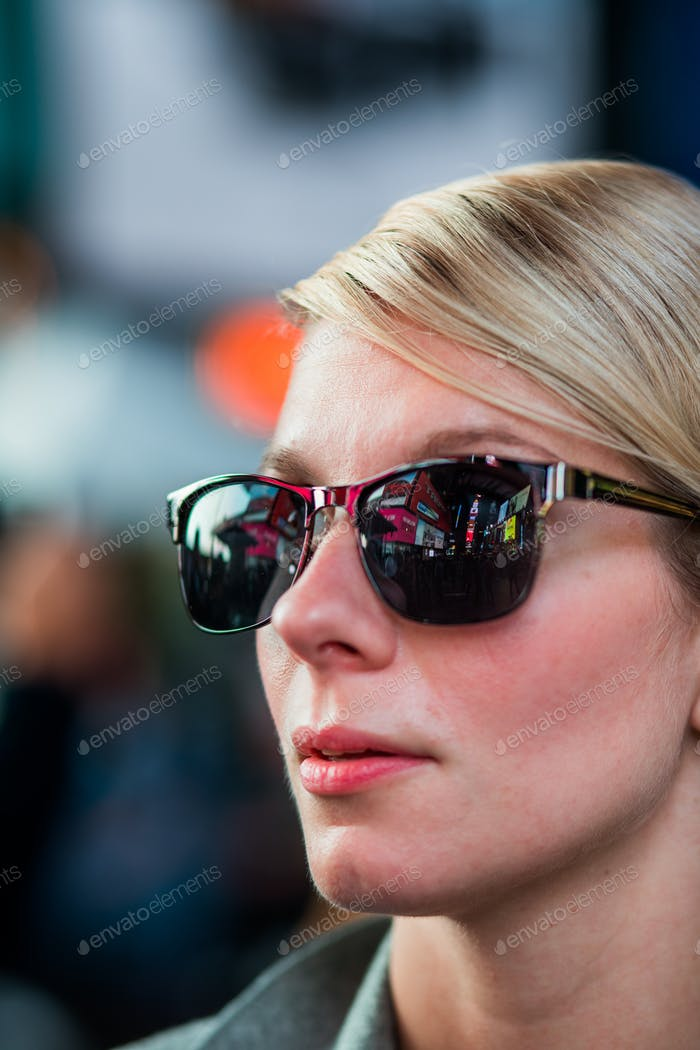 Woman with Time Square Buildings Reflection in Sunglasses at Nig