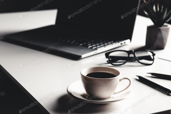 Business man using laptop computer with pen glasses and cup of hot coffee