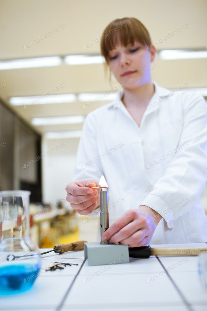 pretty female researcher/chemistry student lighting up a burner