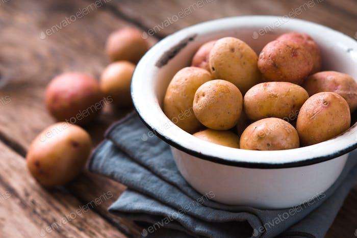 Raw potatoes in a white bowl on a napkin partial blur