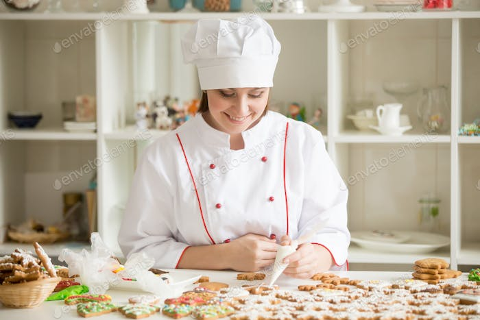 Professional smiling confectioner decorating gingerbread stars