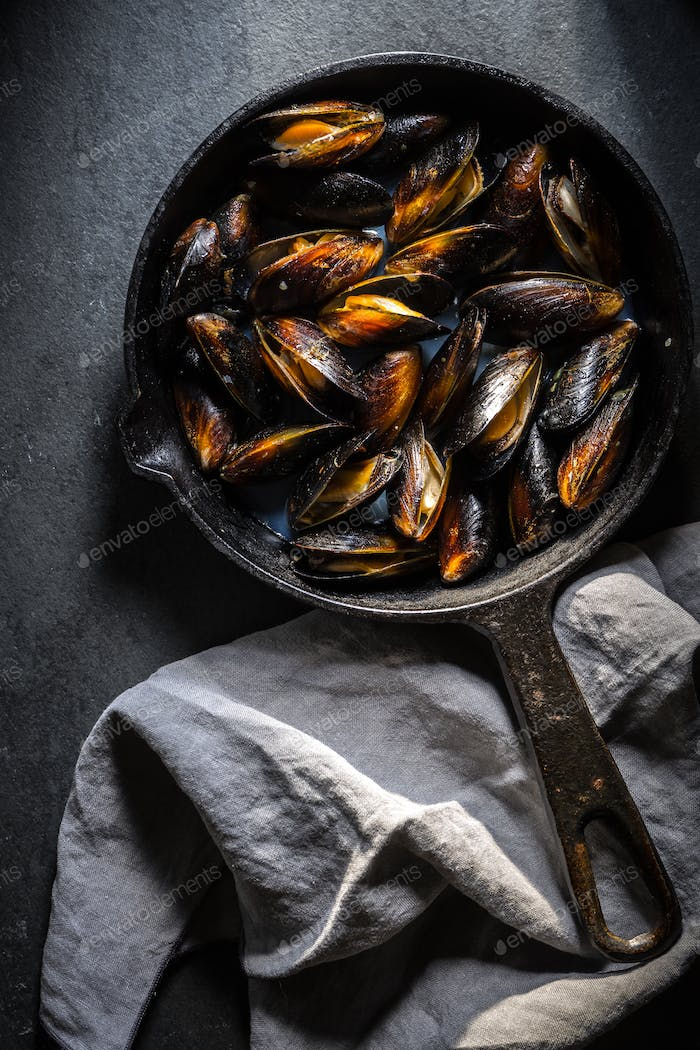 Mussels on a cast-iron frying pan and napkin on a gray background
