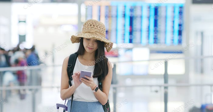 Woman check on the flight number in the airport