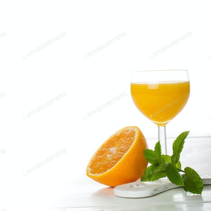 Orange juice in glass with slice of orange.