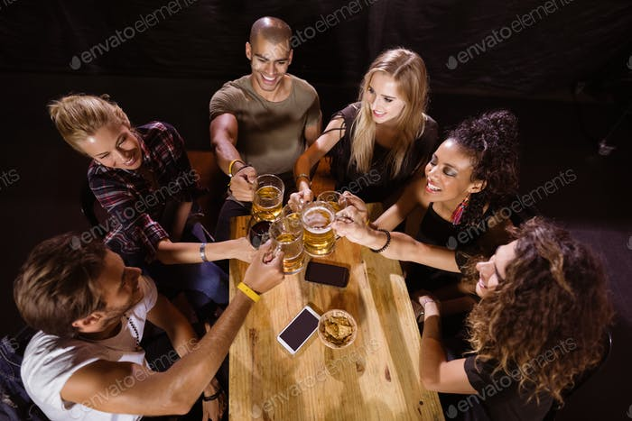 High angle view of happy friends toasting at table