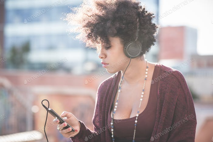 beautiful black curly hair african woman listening music with he