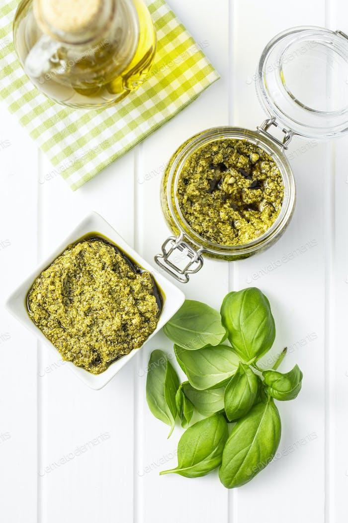 Green basil pesto dip sauce and basil leaves.