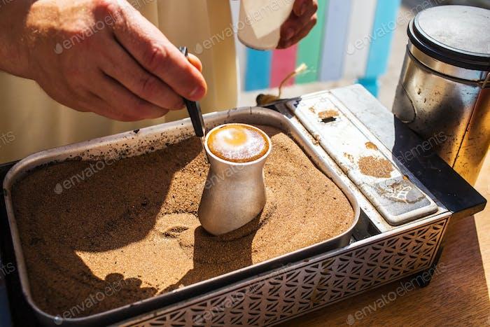 Hand holding coffee turk on sand.
