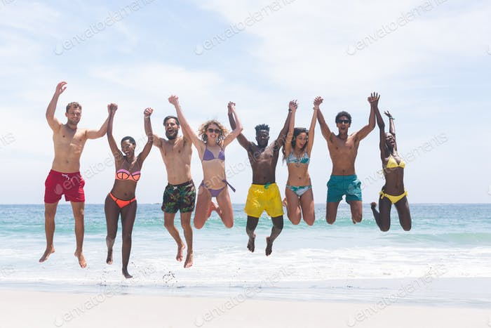 Group of diverse friends enjoying and jumping in water at beach on a sunny day