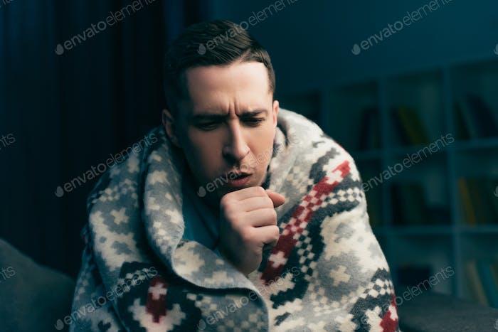 gut aussehender Mann hustet, während er zu Hause Grippe hat