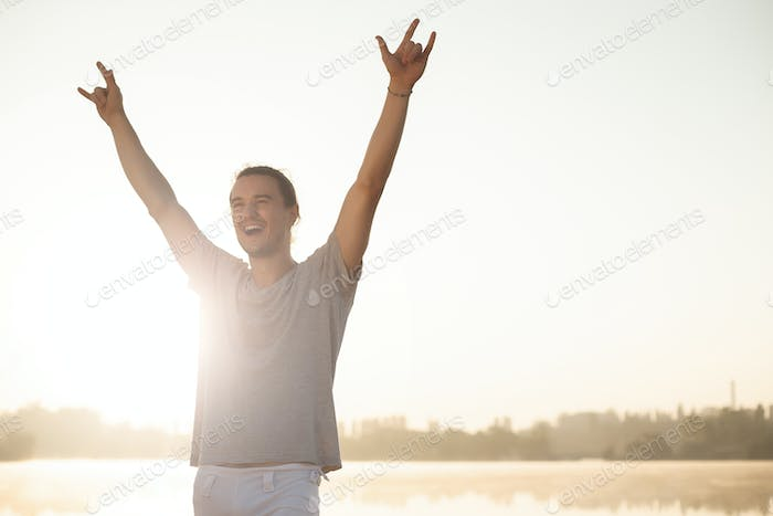 Sweaty man with raised hands happy to finish workout on sunrise