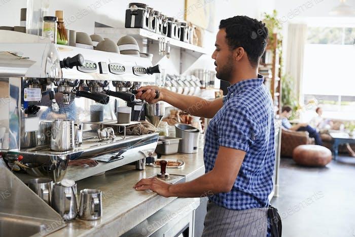 Young male barista preparing espresso at a coffee shop