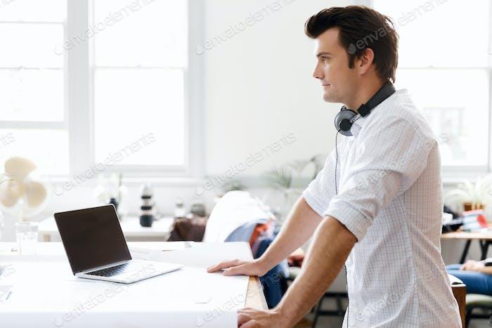 Junger Mann steht im kreativen Büro