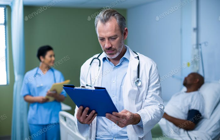 Doctor checking patient report in ward