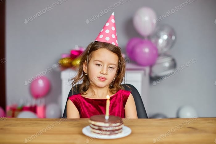 A little girl is wearing a birthday hat makes a wish , looking at a Birthday Cake