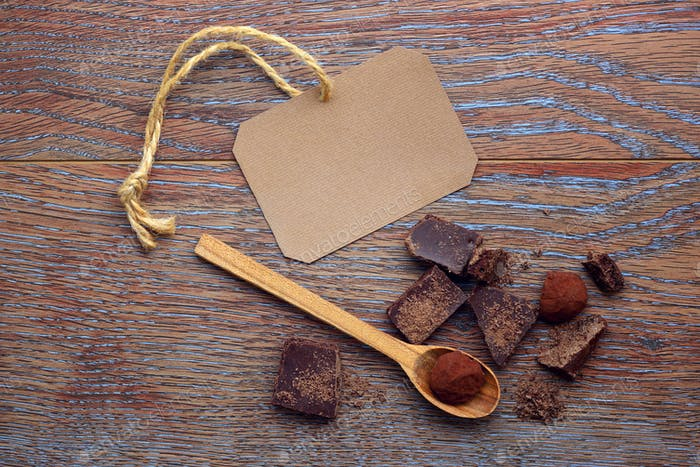 Blank paper sticker with pieces of chocolate and spoon on wooden