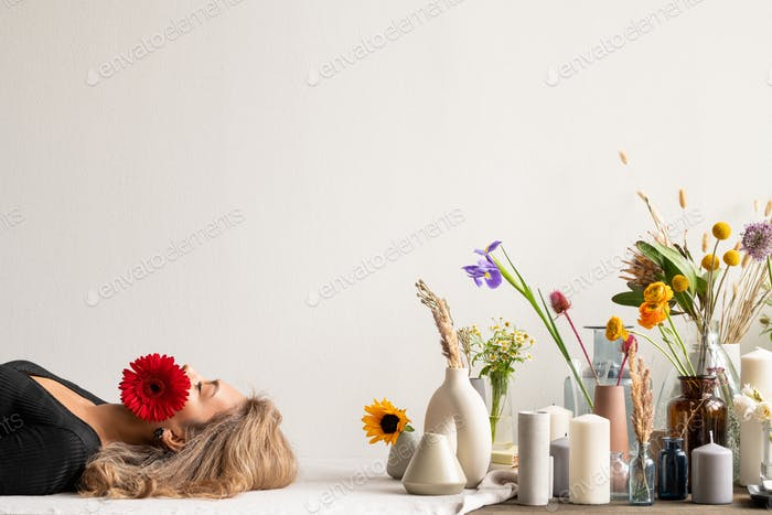 Young serene woman with red herbera in her mouth lying by candles and flowers