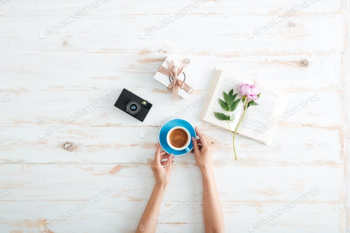 Female hands holding cup of coffee over wooden table