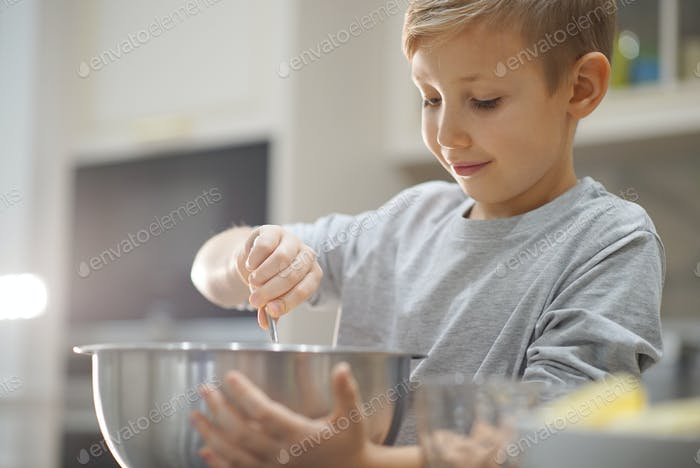 Child cooking at the kitchen. White boy stirring dough for a cookie.