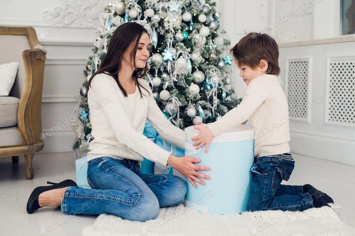 Woman and boy checking christmas presents at home