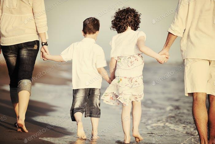 glückliche junge Familie haben Spaß am Strand bei Sonnenuntergang