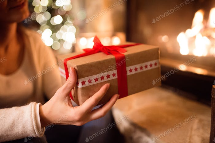 Unrecognizable woman in front of Christmas tree giving present