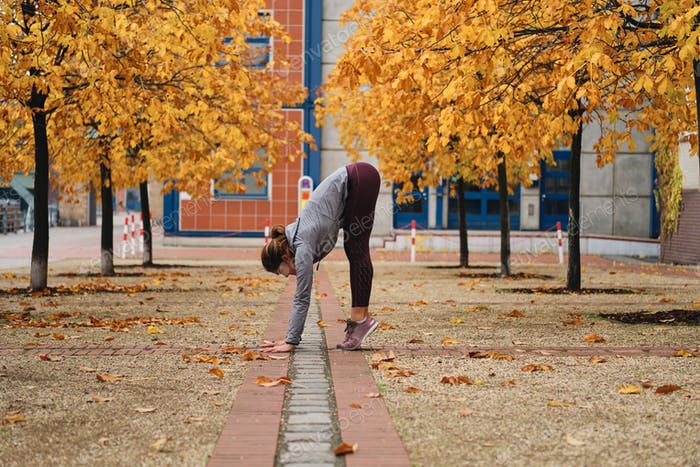 Attractive sporty girl stretching during workout on autumn city street