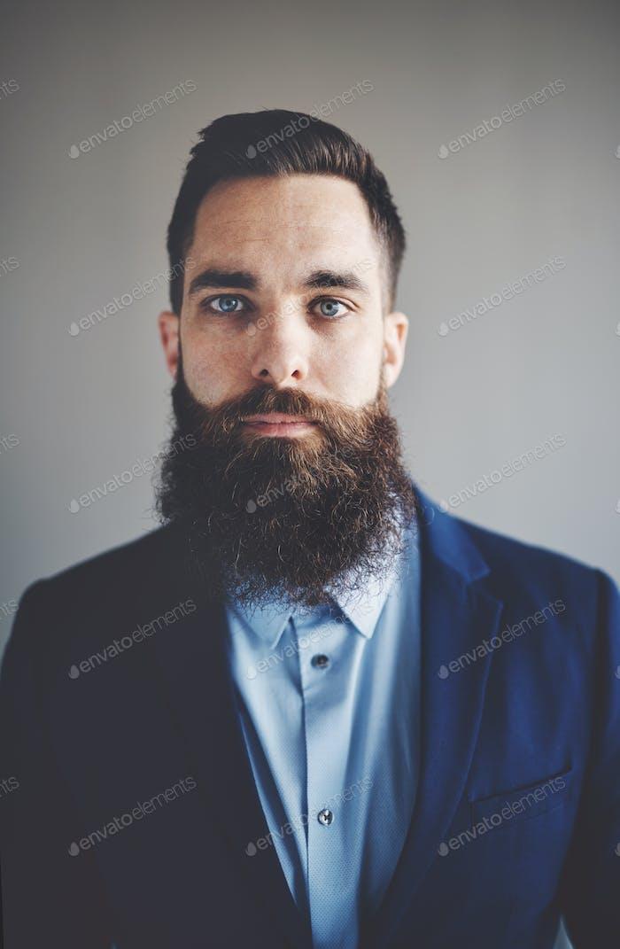 Ориентированный молодой предприниматель с длинной бородой носить блейзер