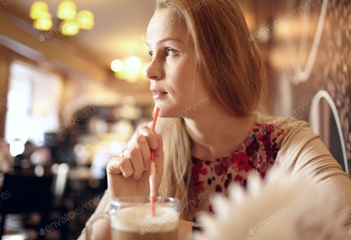 Girl is looking through the window in cafe