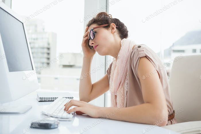 Focused businesswoman with glasses using computer in the office