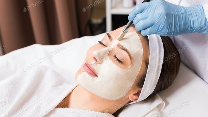 beautician applying cosmetic mask to woman on half  face with cosmetic brush   at beauty salon