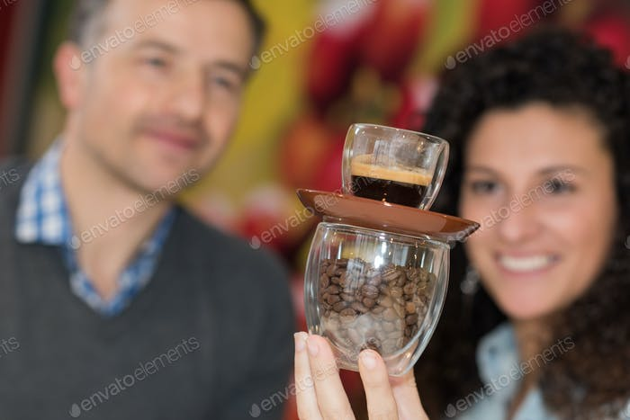 Woman balancing an espresso on a cup of coffee beans
