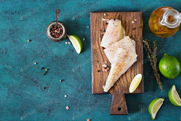 Fillet of white fish on a wooden board prepared for cooking. Flat lay. Top view